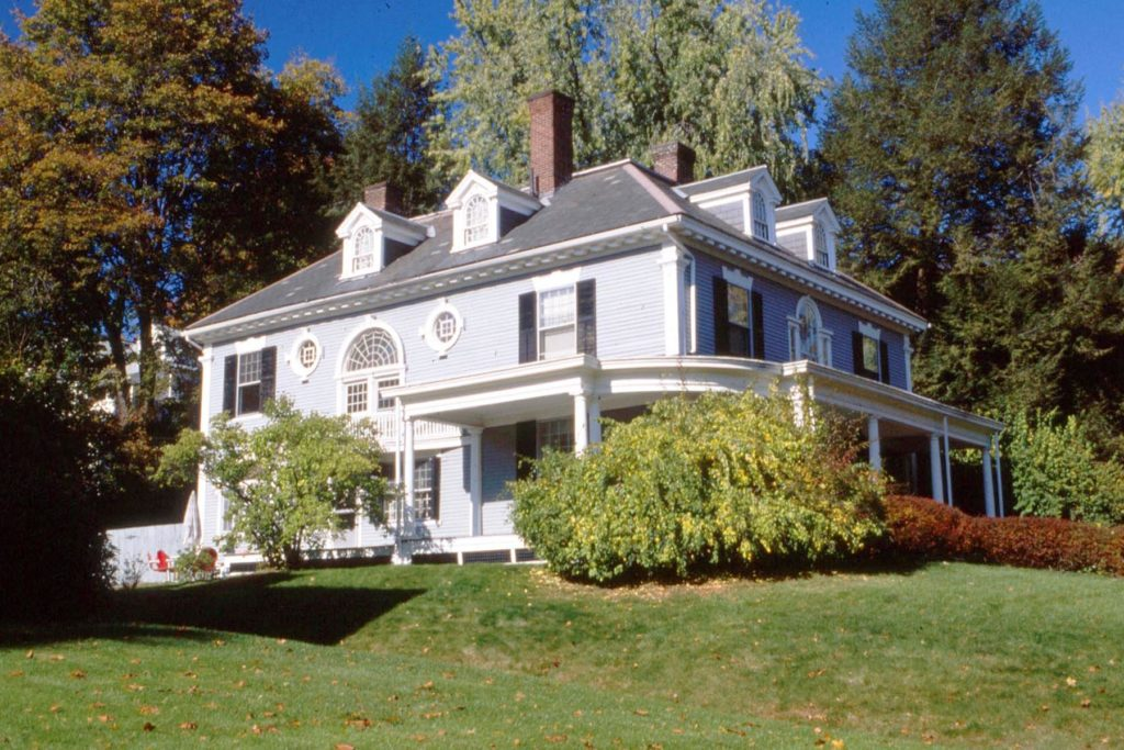 A large foursquare form Colonial Revival Style House with porch dormer and pseudo Palladian window.