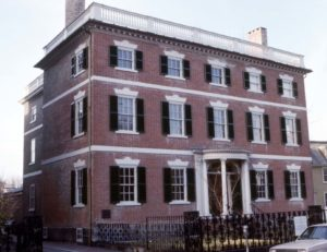 A classic brick Federal with three stories, including a low pitch roof and balustrade