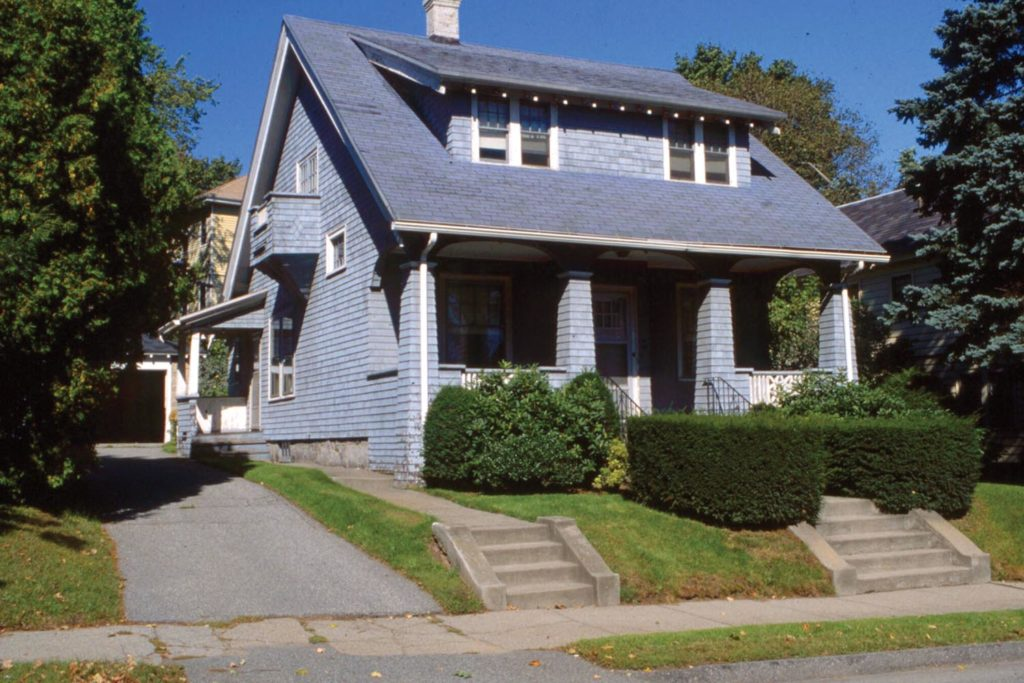 This bungalow has a wood shingle exterior with strong battered porch columns and a low slung dormer.