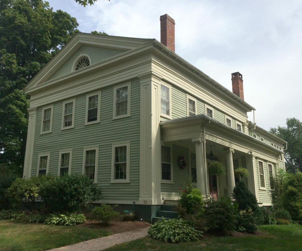 A quirky Greek Revival with the gable end facing the street and a side entrance and a fairly substantial porch with Ionic columns.
