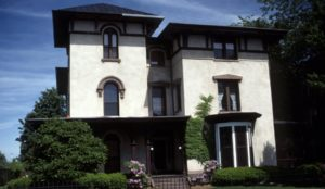 a stately Italianate style with typical low pitch roof and doubled heavy bracketing