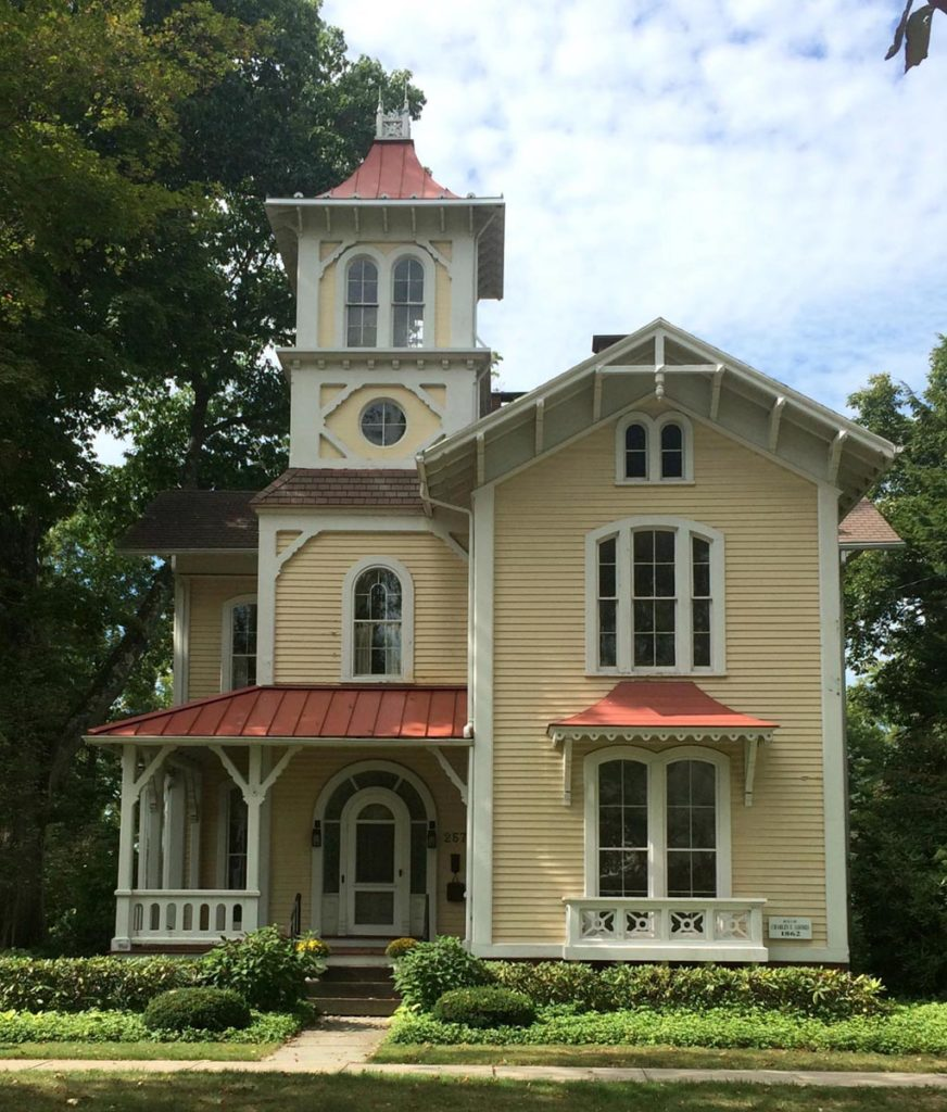 This house is a fine 1850s style Tuscan revival with an asymmetrical massing, tall squared tower (aka campanile), and round-head windows, but it appears to have been augmented with angular Stick Style brackets, corbels and gable ornaments.
