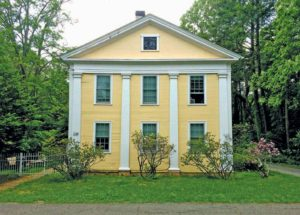 A yellow Greek Revival home with white trim that accentuates the period pilasters.