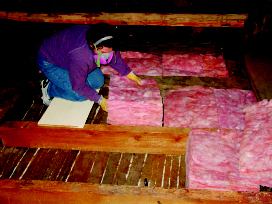 Installing batts insulation in the attic bays. Be sure to wear proper clothing and a mask